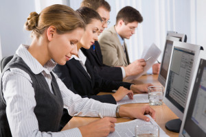 Portrait of confident people sitting in a line in front of monitors and looking at camera