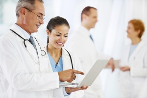 Two successful doctors working on a laptop. The focus is on the young female doctors looking at the laptop. Group of doctors in the background. [url=http://www.istockphoto.com/search/lightbox/9786662][img]http://dl.dropbox.com/u/40117171/medicine.jpg[/img][/url]